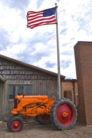 HILLSBORO, NORTH DAKOTA, May 10,2019:  The old Minneapolis Moline R tractor under a flag pole was from the company based in Minnesota, and was the product of a merger between three companies in 1929: Minneapolis Steel & Machinery (MSM), Minneapolis Thres Editorial