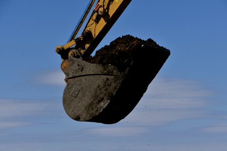 The huge bucket of an excavating machine is filled with black soil.