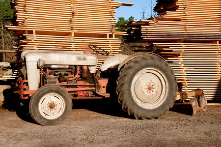 ROWLEY, MASSACHUSETTS:  The old Ford N Series tractor parked by a sawmill  is a product produced by Ford  Motor Co. between 1939 and 1952, spanning the 9N, 2N, and 8N models. Imagens - 123572681