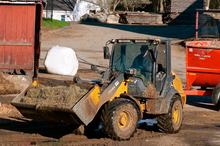 ROWLEY, MASSACHUSETTS, April 28, 2019: The 204K John Deere front end loader hauling silage is a product of John Deere Co, an American corporation that manufactures agricultural and construction equipment, drive trains, and transmission.