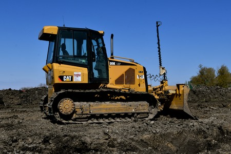 MOORHEAD, MINNESOTA, May 9, 2019: Founded in 1925, the 319D Cat excavator pushing  earth is from Caterpillar Inc., an American corporation which designs, develops, engineers, manufactures, markets and sells machinery, engines, financial products.