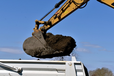 The bucket of a backhoe prepares to dump black dirt into a truck box Imagens - 123610652