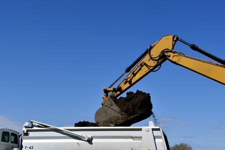 The bucket of a backhoe prepares to dump black dirt into a truck box Imagens - 123610653