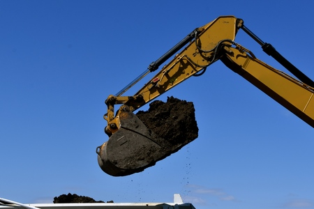 The bucket of a backhoe prepares to dump black dirt into a truck box
