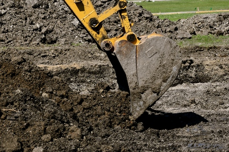 A bucket from an excavator scrapes a load of earth from a future building site.