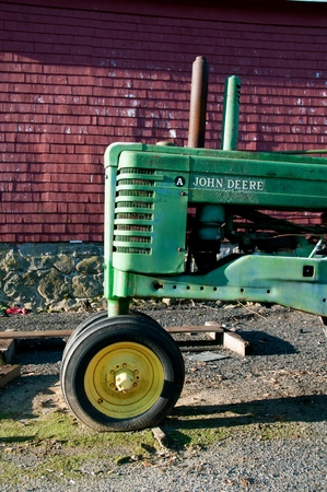 ROWLEY, MASSACHUSETTS, April 28, 2019: The old A John Deere tractor parked in front of a red barn iis a product of John Deere Co, an American corporation that manufactures agricultural and construction equipment, drive trains, and transmission.