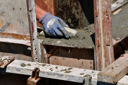 Concrete worker trowels wet mud(concrete) on the footings of a new construction building site. Imagens - 123610688