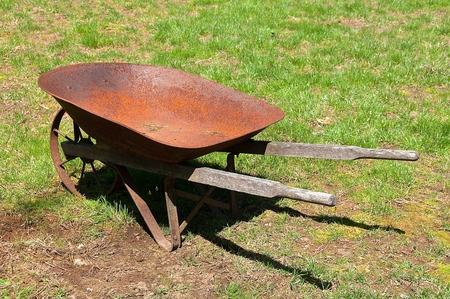 An old rusty metal wheelbarrow with wood handles rests in a yard.