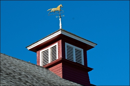 A cupola on a ranch stable barn displays a weather vane with a horse trotting.