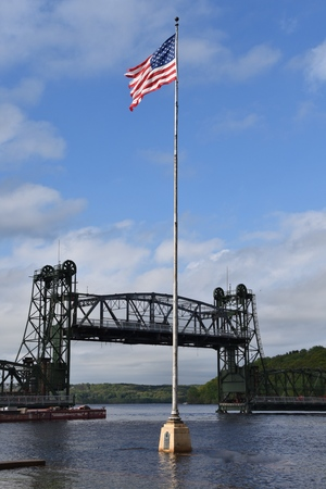 The USA flag stands in water on the flooded St. Croix River with a lift bridge in the background.