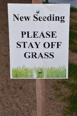 Sign indicates staying off grass due to new seeding.