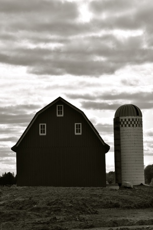 An old hip roofed barn and stave silo are silhouetted in the the cloudy sky. (black and white) Stok Fotoğraf