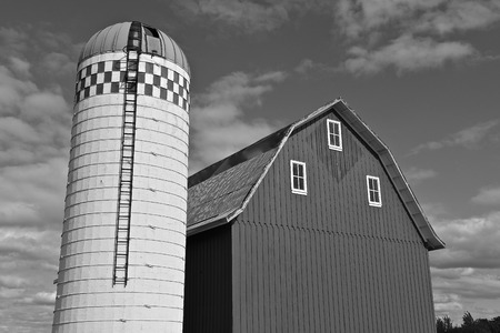 An old silo and  hip roofed barn which has steel siding  (black and white) Imagens