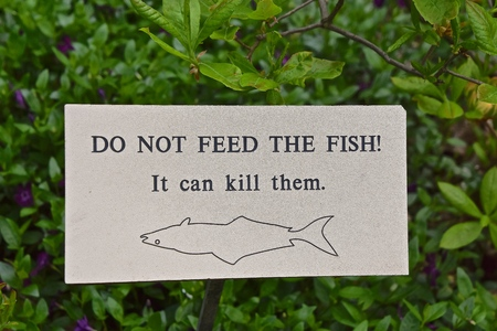 An outdoor pond sign prohibit feeding the fish with an upside down fish depicting `death`.