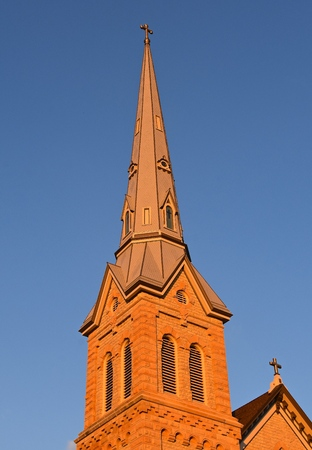 The evening sun shines upon the steeple of an old brick church