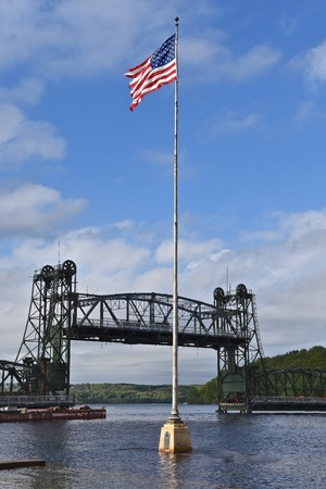 The USA flag stands in the flooded river of the St. Croix with a lift bridge in the background