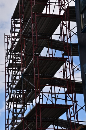 Levels of scaffolding are silhouetted against the sky on the remodeling of a huge building