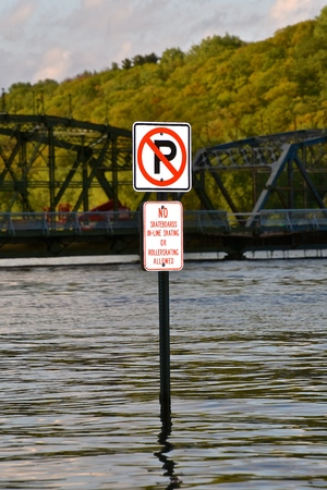 A sign partially submerged in a swollen river does not allow parking , rollerskating, or skateboards. Imagens - 124628518