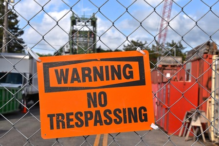 A `Warning No Trespassing` sign is posted on a gate of a construction site.
