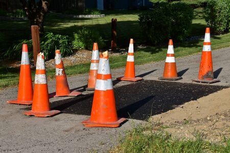 Orange warning cones surround an asphalt repair job on a sidewalk bike path.