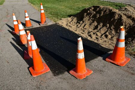 Orange warning cones surround an asphalt repair job on a sidewalk bike path.