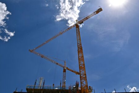 Several construction tower cranes extended over a building under construction  silhouetted against the clear blue sky. Imagens