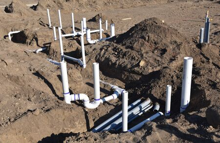 Pvc pipe is installed and buried under the ground prior to the cement floor being poured on a new construction site.