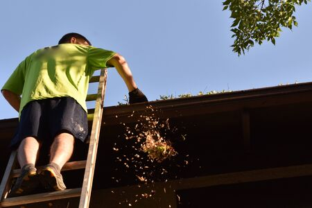 An unidentified man stands on an extension ladder cleaning the eaves and gutters of a two story house