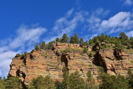 The beauty of a steep cliff with layers of rock formation is located in the Black Hills of South Dakota.