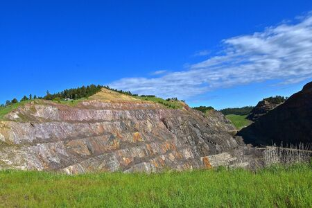 The rock cutting of a huge hill removed from the side of a hill displays the cuttings of the layers of rock in an open mine pit in the search for gold