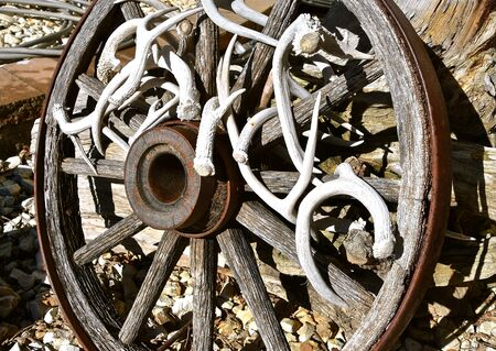 An old wooden wagon wheel is decorated with deer antlers Stockfoto