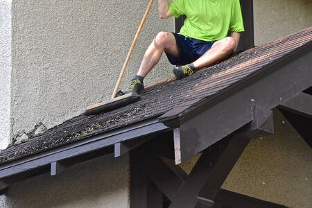 An unidentified man sits on an entryway porch of a house sweeping the roof from leaves, seed, and residue. Stockfoto