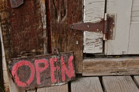 An old wooden and rustic door with a rusty hinge has a sign painted in bright lettering stating they are open.