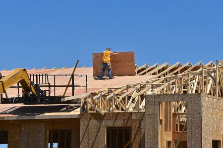 An unidentified construction worker moves a sheet of plywood into place on a roofing project of a new wood structure.