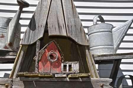 A red old primitive birdhouse is surrounded by vintage water springer cans