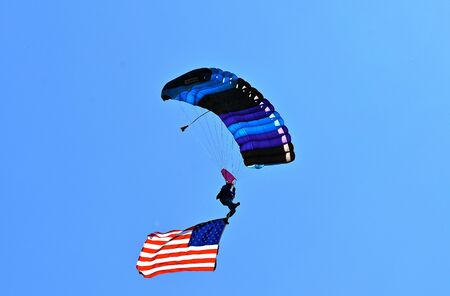 The operator of a hang glider travels through the sky with the American flag attached to a boot.