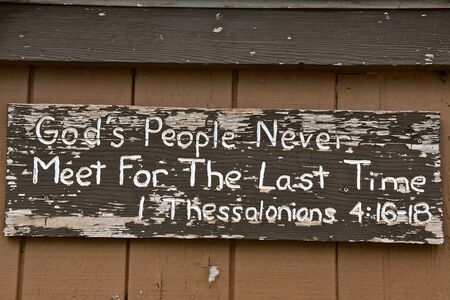 Bible verse on an old peeling wooden sign from Thessalonians referring to Gods people