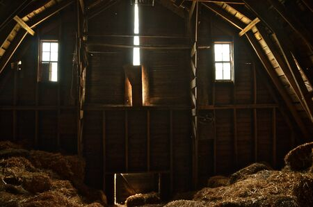 Interior of an empty hayloft of a barn with light streaming in through the windows and crack in the doors