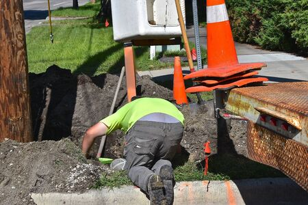 Electricians work in a hole underground repairing electric wiring by a wooden utility pole.