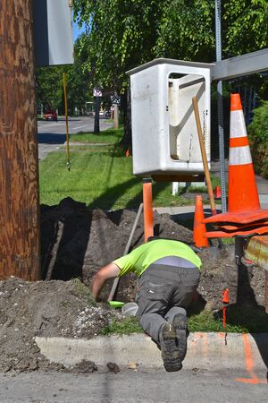 Electricians work in a hole underground repairing  electric wiring by a wooden  utility pole. Imagens