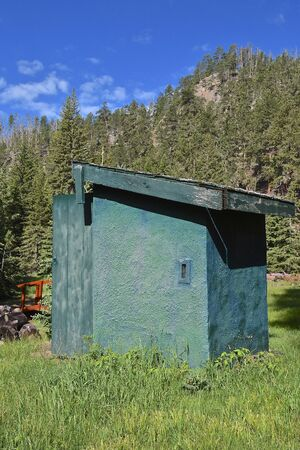 An old green outhouse located in a mountainous and wooded area. 스톡 콘텐츠 - 127852596