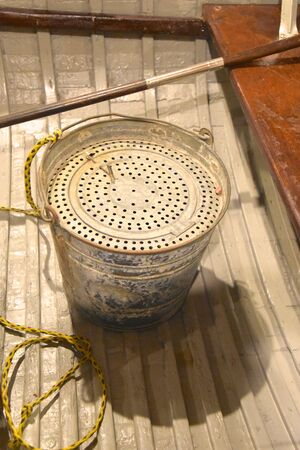 An old bait pail for storing minnows lies in the bottom of a metal boat