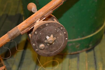 A very old fishing rod and reel is located one an equally old boat.