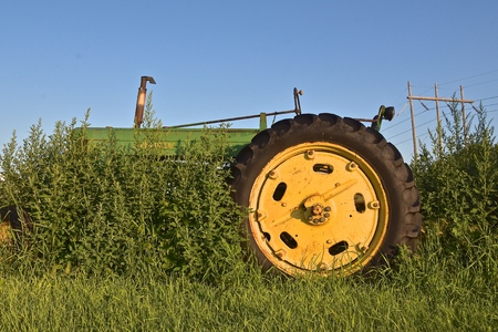 MOORHEAD, MINNESOTA, July 21, 2019:  The old A John Deere tractor surrounded by all weed is a product of John Deere Co, an American corporation that manufactures agricultural and construction equipment, drive trains, and transmission.