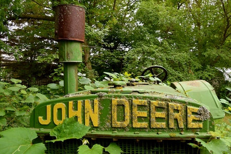 LOWRY, MINNESOTA,  July 28, 2019: The old D John Deere tractor buried with foliage iis a product of John Deere Co, an American corporation that manufactures agricultural and construction equipment, drive trains, and transmission.