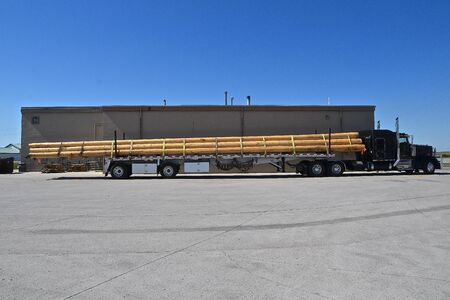 A semi and trailer parked in a lot is loaded with extra long fir poles