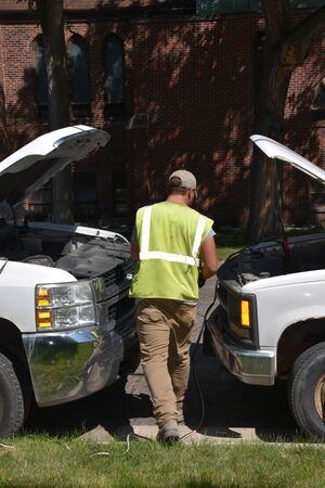 An unidentified mechanic is jump starting a truck with a dead battery .