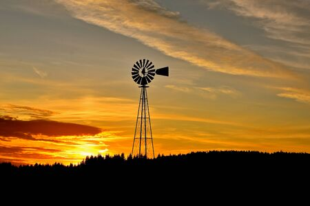 An old farm windmill is silhouetted against the colorful sunset in the west. Imagens