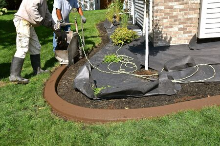 Environmental designers are forming concrete edging around a flower bed of a home