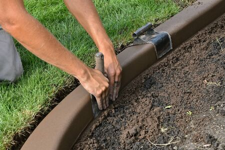 Troweling and shaping for smoothness in a freshly created concrete edging around a flower bed